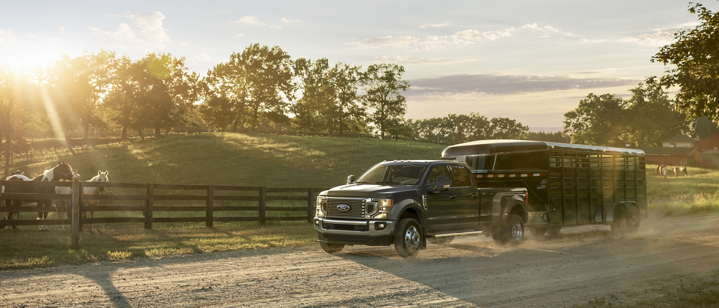 2020 Ford Super Duty towing a trailer on a ranch with horses in the background