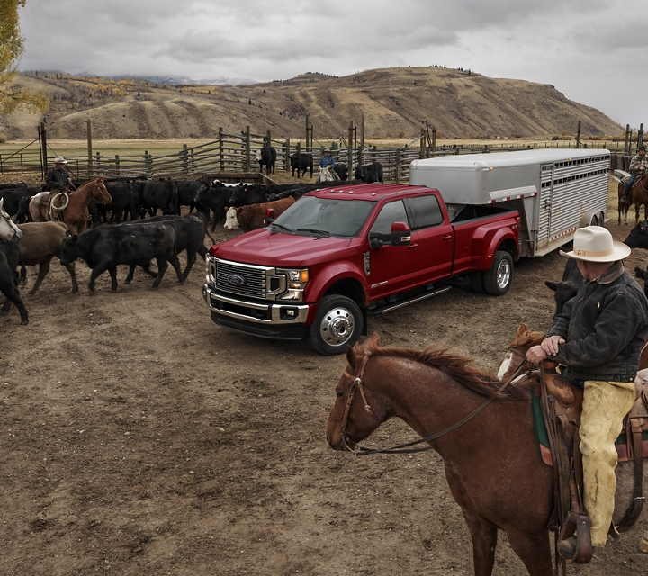 Ranchers on horses watch as a 2020 Super Duty tows a horse trailer