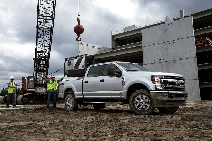 Crane loading cargo into bed of 2020 Ford Super Duty F 2 50 S T X in Iconic Silver at worksite