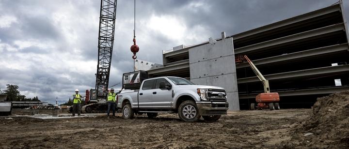 Trabajadores de la construcción cargan una gran pieza de maquinaria en la plataforma de una Super Duty 2020