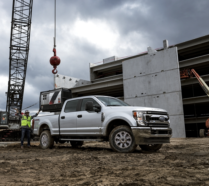 Construction workers load a large piece of machinery into the bed of a 2020 Super Duty