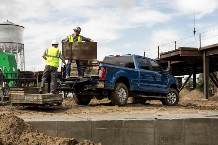 Workers unloading wood pallets from a 2020 Ford Super Duty F 2 50 S T X