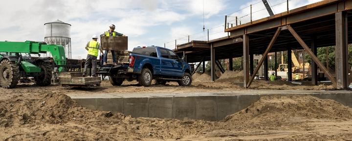 Un trabajador de la construcción carga formas de concreto en la plataforma de una Super Duty 2020