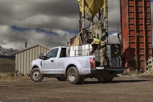 2020 Ford Super Duty with workers loading cargo in pickup bed