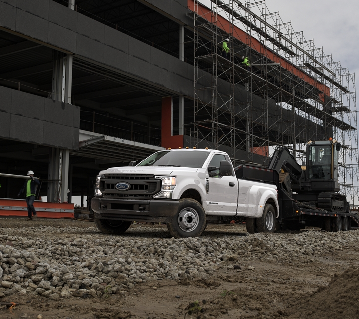 A 2020 Super Duty tows a piece of heavy machinery on a construction site