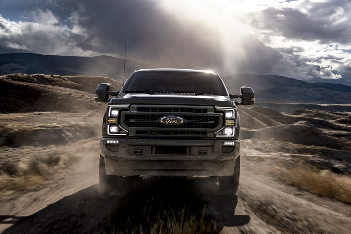 2020 Ford Super Duty LARIAT with Sport Appearance Package in Magnetic being driven down a dirt road near hills