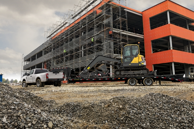 Rear view of 2020 Ford Super Duty on a large scale building job towing a backhoe
