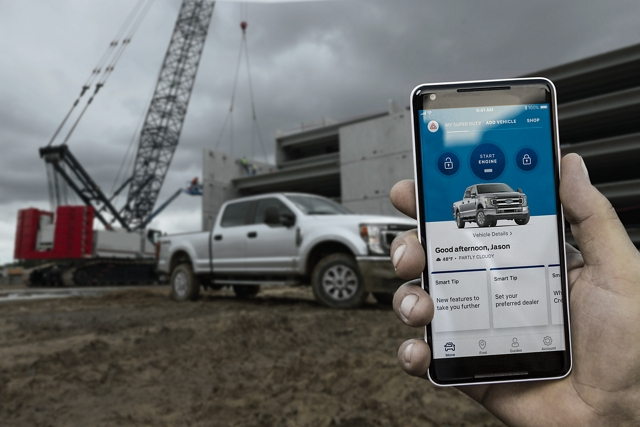 Hand holding smartphone on a job site with 2020 Ford Super Duty in the background
