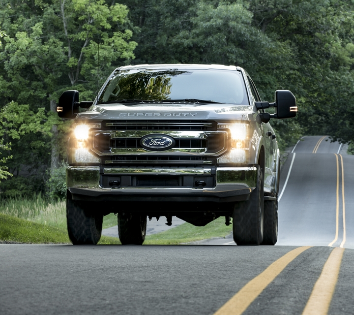 2020 Ford Super Duty F 3 50 X L T Crew Cab with Tremor Package in Ingot Silver being driven on a tree lined road