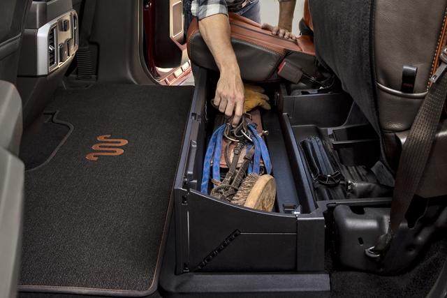 Hombre tomando herramientas de la caja de almacenamiento con seguro en el asiento trasero