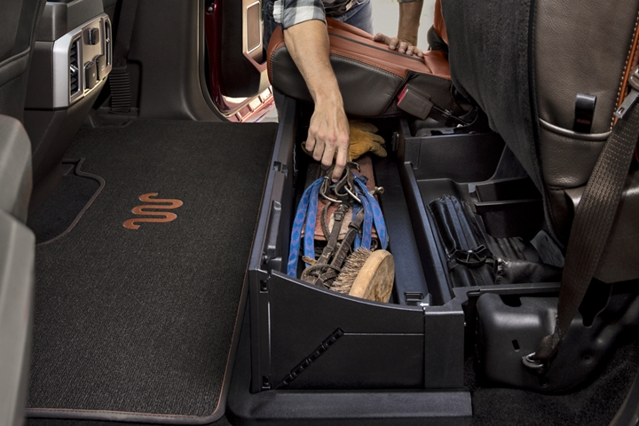 2020 Ford Super Duty with cowboy reaching into lockable under seat storage box in the second row