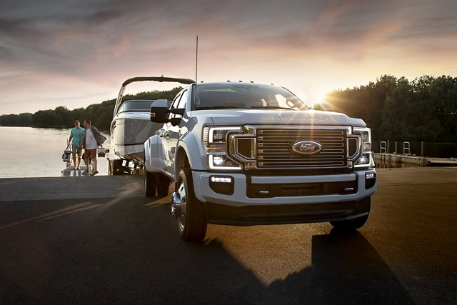 2020 Ford Super Duty parking boat into a lake with people in the background carrying fishing equipment