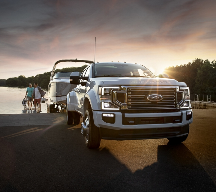 2020 Ford Super Duty F 4 50 Limited Crew Cab in Star White parking a boat into a lake while people with fishing gear wait in the background