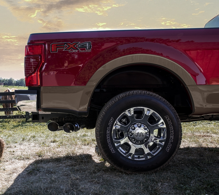 Shot of rear of 2020 Ford Super Duty with Chrome Package in Two Tone Rapid Red next to woman picking up a bundle of hay