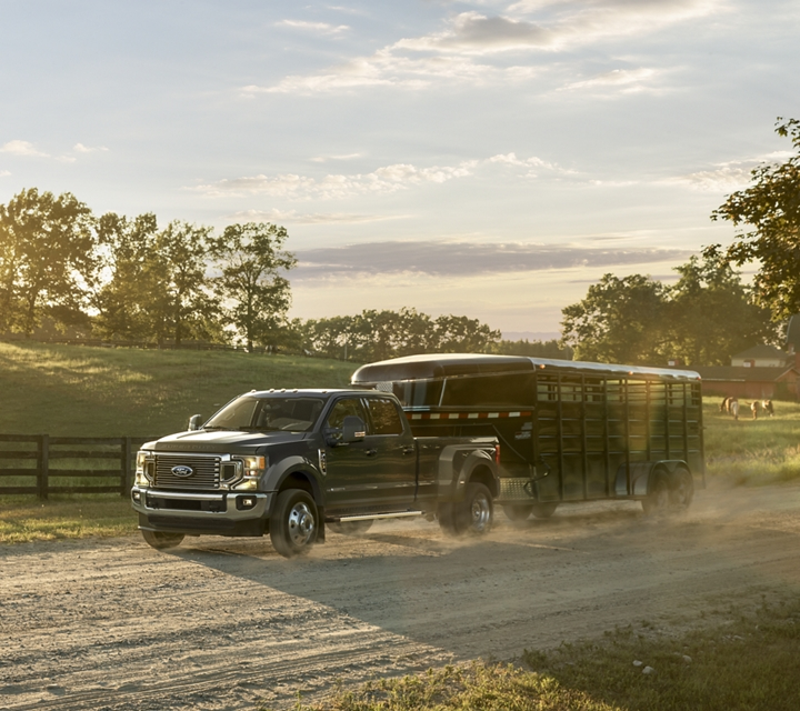 2020 Ford Super Duty F 4 50 Lariat Crew Cab in Blue Jeans towing a trailer on dirt road on farm