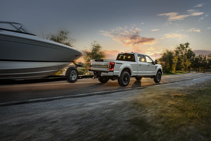 2020 Ford Super Duty Platinum F 2 50 Crew Cab with Tremor Off Road Package in Star White Metallic towing a boat on road at sunset