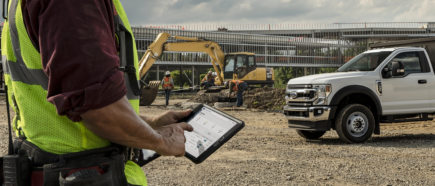 Man on job site standing next to a 2020 Ford Super Duty looking at his tablet