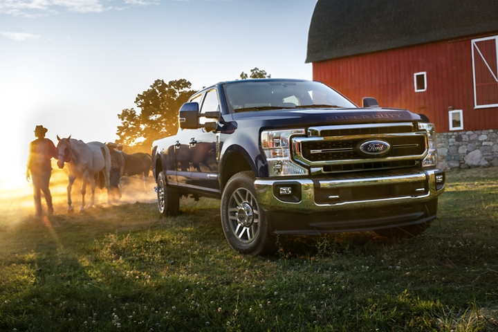 2020 Ford Super Duty LARIAT Crew Cab in Blue Jeans with rancher and horse behind it on a farm
