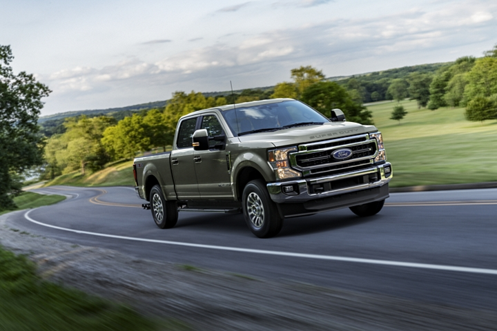 2020 Ford Super Duty LARIAT Crew Cab in Silver Spruce being driven on curvy road near trees and grass