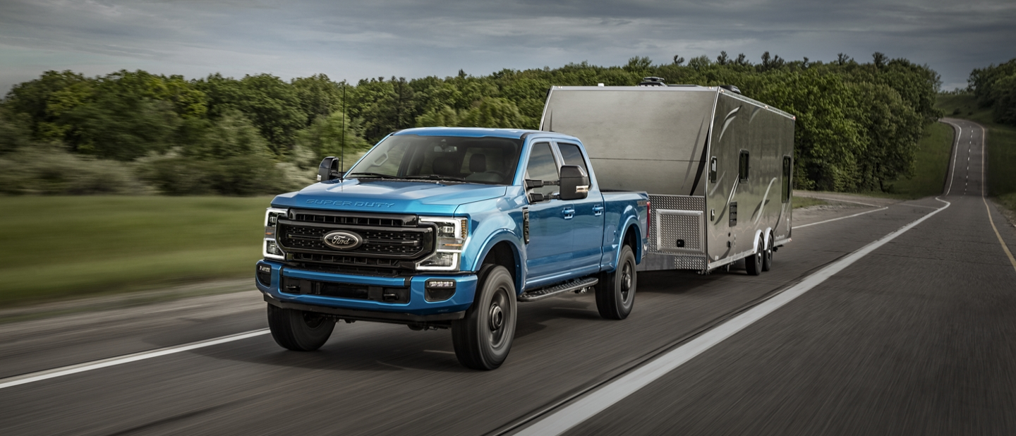2020 Ford Super Duty being driven on a road towing a trailer
