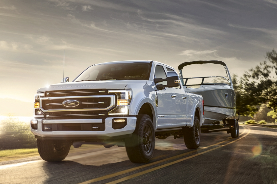 2020 Ford Super Duty Platinum Tremor in Star White Metallic towing a boat