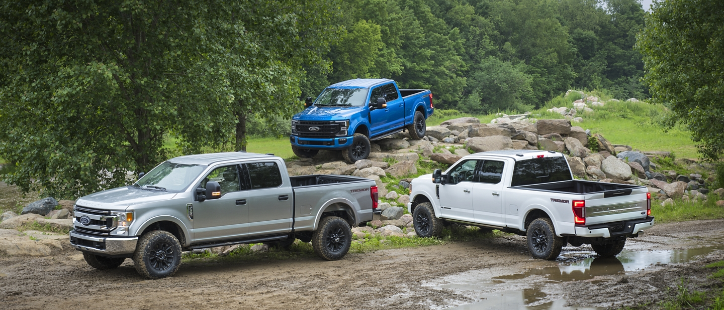 Three 2020 Ford Super Duty models parked in dirt path near rocks trees and mud
