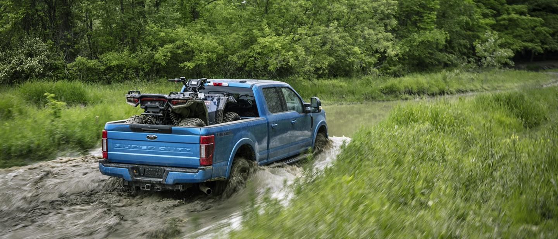 La Ford Super Duty Lariat F 2 50 2020 con Paquete Todo Terreno Tremory crewcab conpaquete de apariencia deportiva enVelocityBlue andando por el agua.