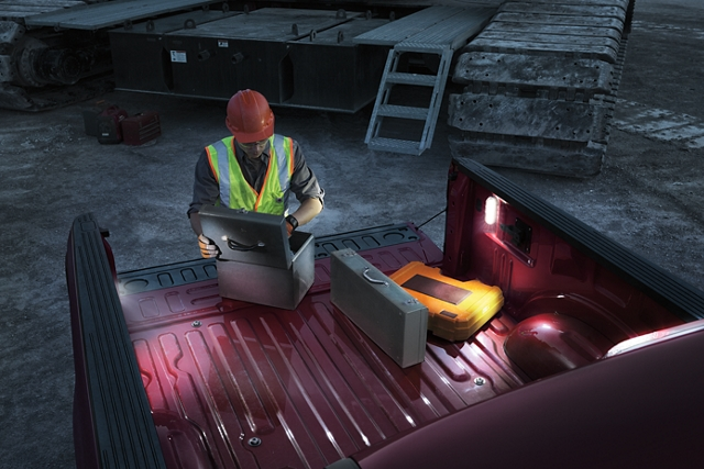 Man working at night in pickup bed with L E D lighting