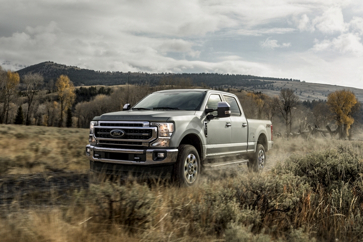 2020 Ford Super Duty F 2 50 LARIAT Crew Cab in Silver Spruce driving on grass