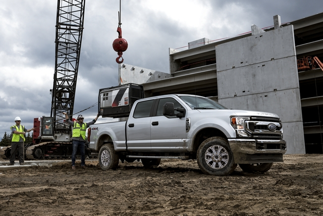 2020 Ford Super Duty on construction site having equipment lowered into bed