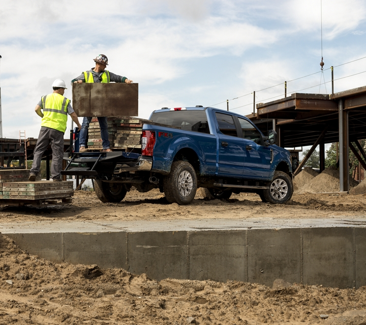 Men unloading the bed of a 2020 Ford Super Duty X L with S T X Appearance Package and F X 4 Off Road Package in Velocity Blue