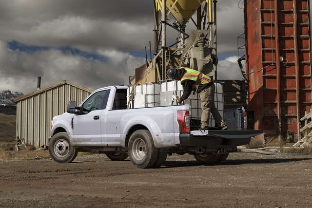 Worker securing heavy load in pickup bed of 2020 Ford Super Duty