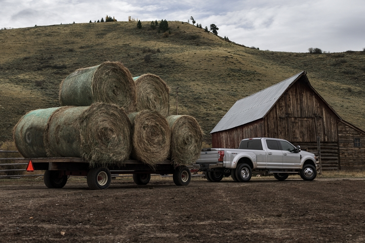 2020 Ford Super Duty F 3 50 LARIAT D R W Crew Cab towing large bales of hay