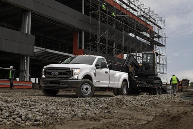 Una Ford Super Duty 2020 con enganche cuello de cisne remolcando equipo de construcción