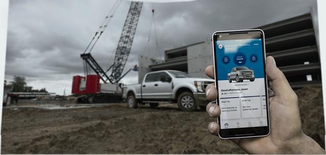 Mano sosteniendo unsmartphone en un sitio de construcción con unaFordSuper Duty 2020 de fondo