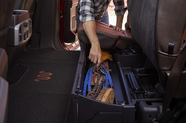 Un trabajador de la construcción tomando una herramienta del almacenamiento del asiento trasero y lacaja con seguro debajo del asiento