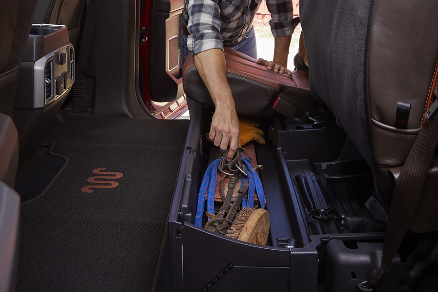 Construction worker grabbing a tool out of the rear seat storage and lockable under seat storage box