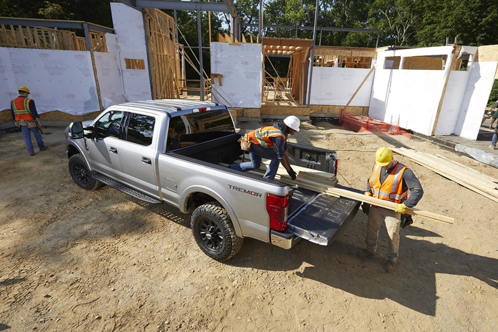 Men taking planks of wood out of the back of 2020 Ford Super Duty X L T Crew Cab with Tremor Off Road Package