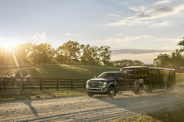 2020 Ford Super Duty F 4 50 LARIAT D R W Crew Cab in Blue Jeans towing a trailer down a country road