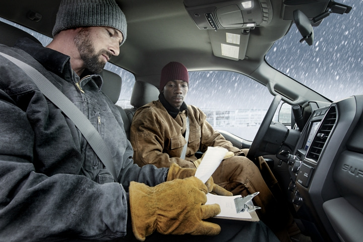Interior of 2020 Ford Super Duty with 2 workers in cold weather gear