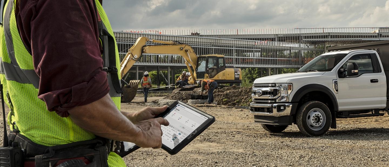 Hombre en un sitio de trabajo mirando su tablet parado al lado de unaFordSuper Duty2020