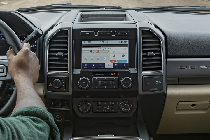 2020 Ford Super Duty X L T in Medium Light Camel interior with person at the wheel and waze on the screen
