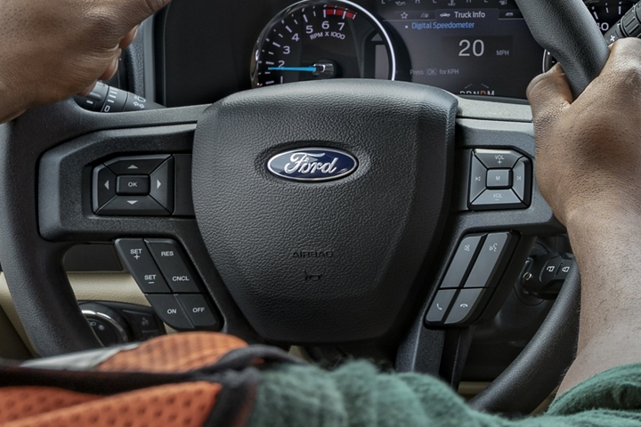 Driver with both hands on steering wheel in 2020 Ford Super Duty Limited with alert on instrument panel