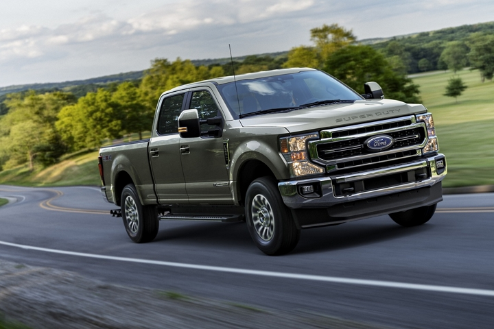 2020 Ford Super Duty F 2 50 LARIAT in Silver Spruce being driven down road near trees