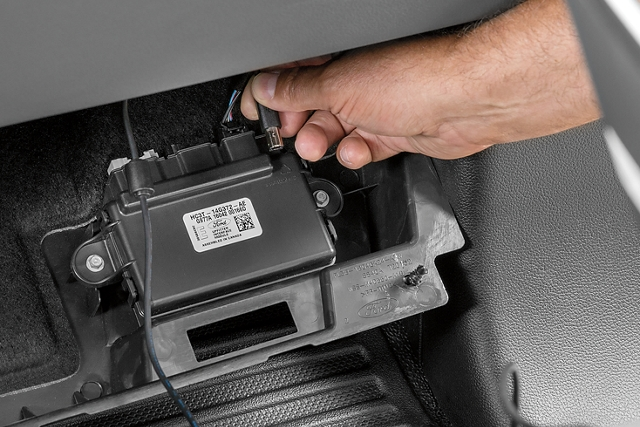 Man connecting cable to upfitter interface module in 2020 Ford Super Duty