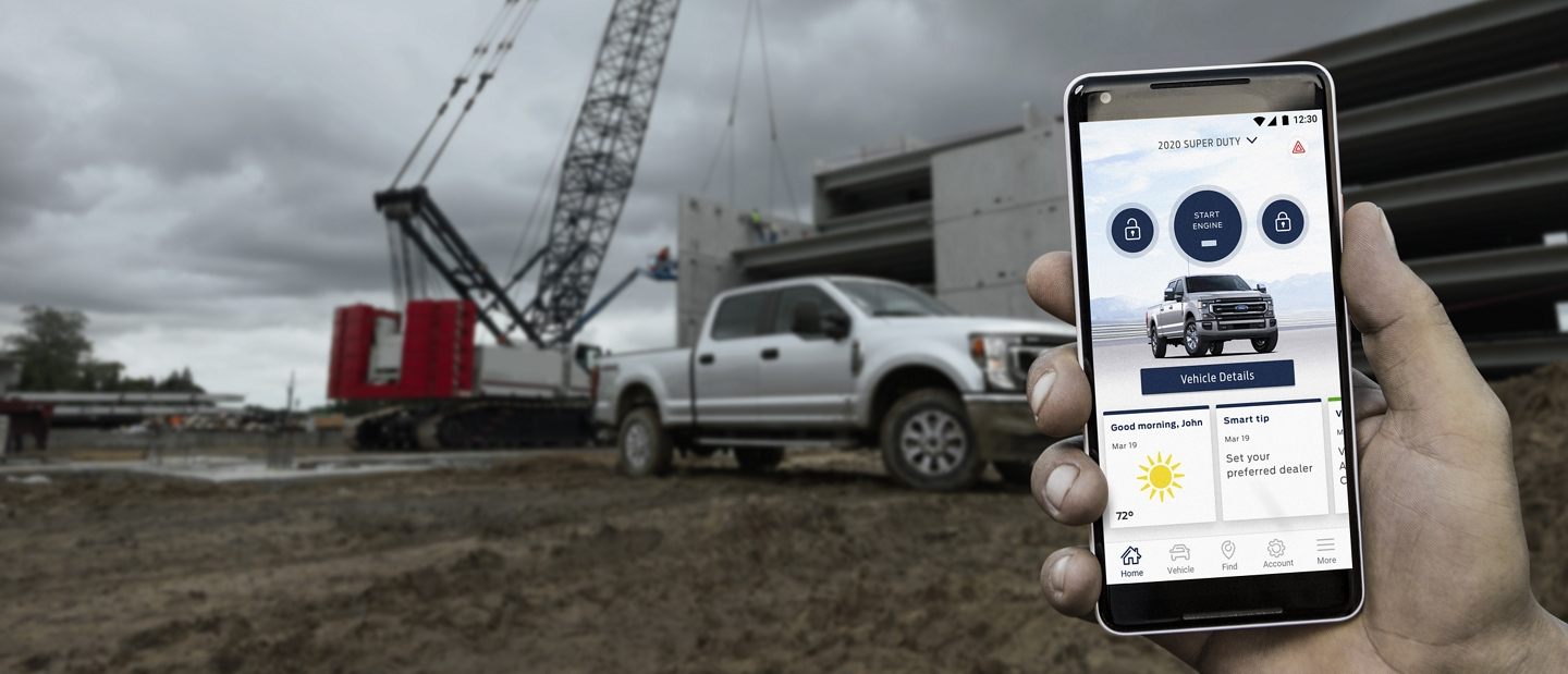 A hand holds a smartphone displaying a Super Duty pickup in the FordPass App