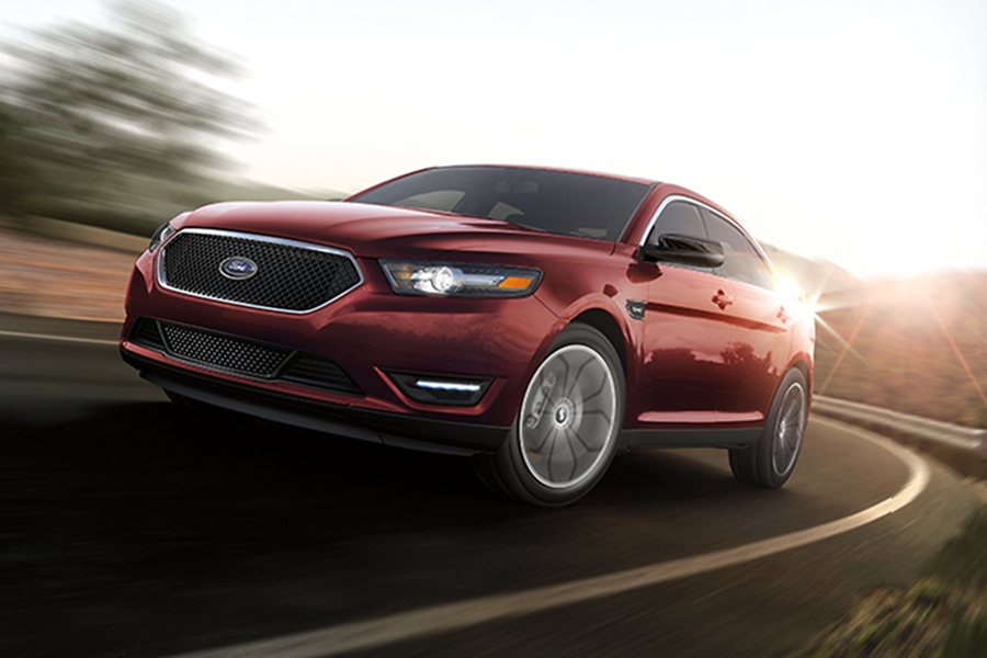 A Ford Taurus being driven around a curve with a blurred background