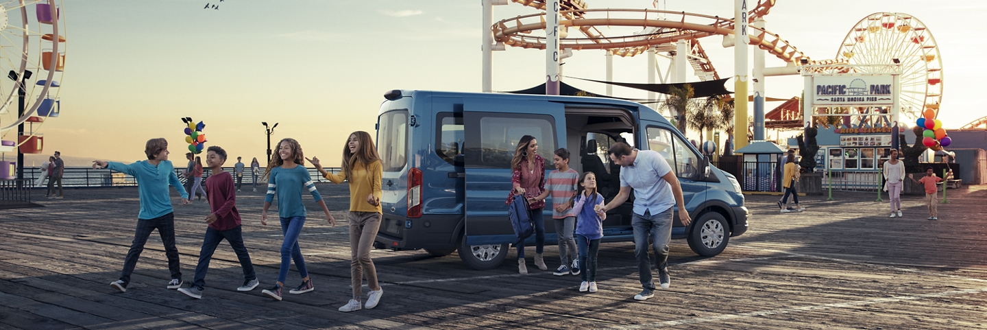 A family walking away from a 2020 Ford Transit at a carnival