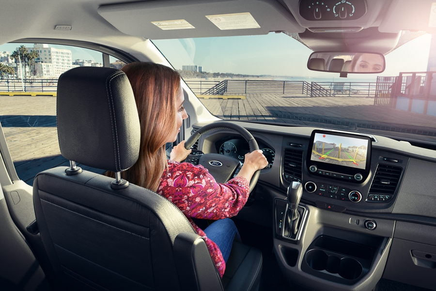A woman behind the wheel of a 2020 Ford Transit on a nice day by a pier