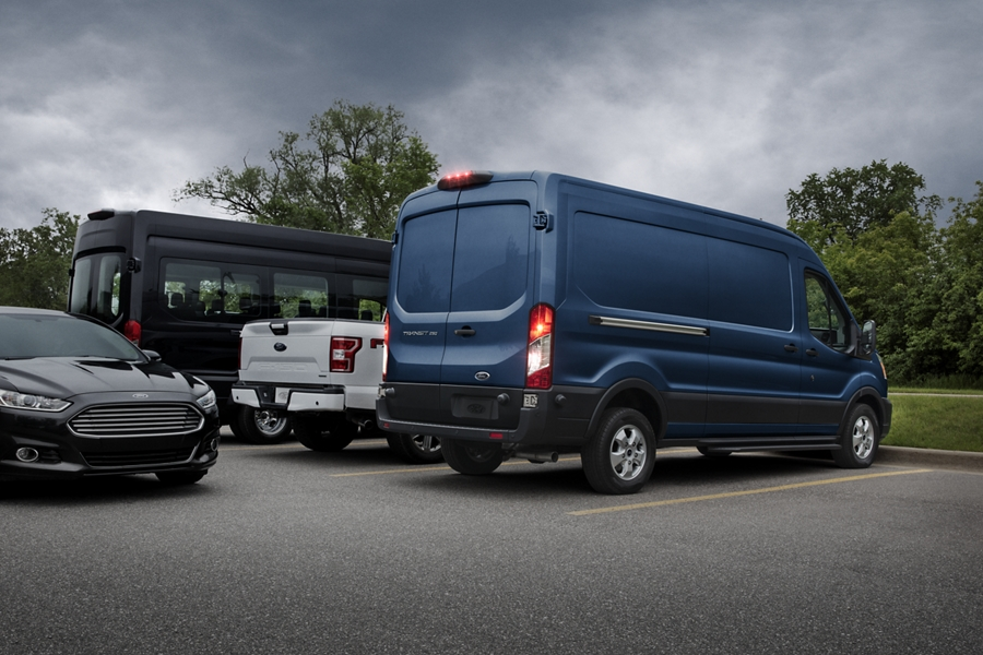 A 2020 Ford Transit Commercial being backed out of a parking spot as another vehicle passes behind